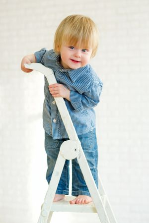 depositphotos 25560563 cute little boy posing from the top of the ladder