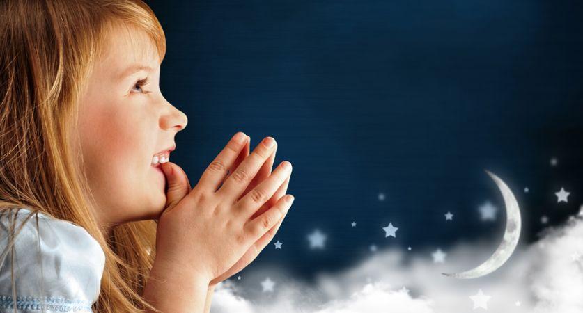 depositphotos 14601359 portrait of little smiling praying girl in blue dress against da